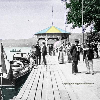 Pörtschach, Werzer Strand, Kärnten. Elegant gekleidete Gesellschaft am Bootssteg am Wörthersee. Historische Aufnahme um 1915, koloriert.