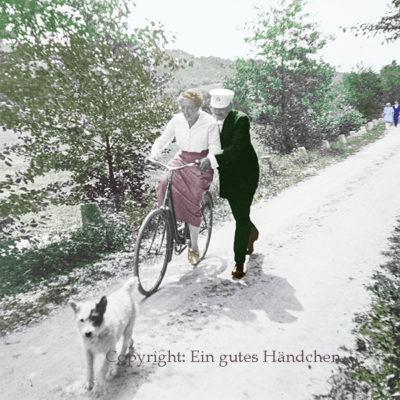 Fahrradlektion anno dazumal. Eine Dame lernt von ihrem Mann radfahren. Im Vordergrund der Familienhund.